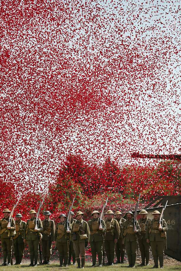 Thousands of poppies, real poppies not the ceramic variety, rain down on Great War Society living history enthusiasts dressed as soldiers of the 4th Battalion, the Middlesex Regiment, in Bovington, England. The poppies represent the dead of World War I, which for England, began Aug. 4, 1914, when Great Britain declared war on Germany. Photo: Peter Macdiarmid, Getty Images
