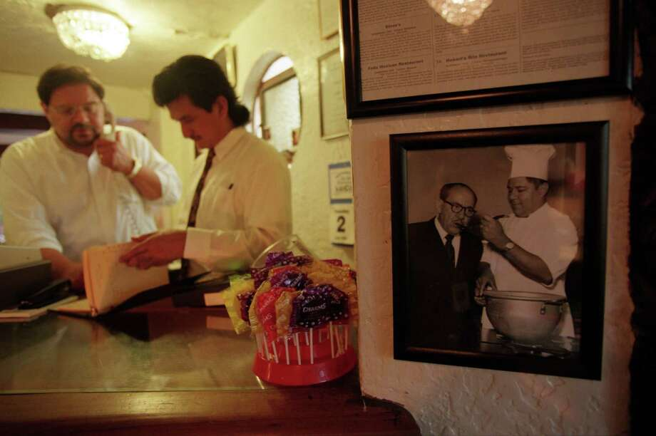In this 1998 photo, Felix Tijerina Jr., left, answers the phone at Felix Mexican Restaurant; a photo of his father hangs to the right. Felix Jr. and sister Janie grew up in the apartment above the restaurant. Photo: Smiley N. Pool, Houston Chronicle / Houston Chronicle