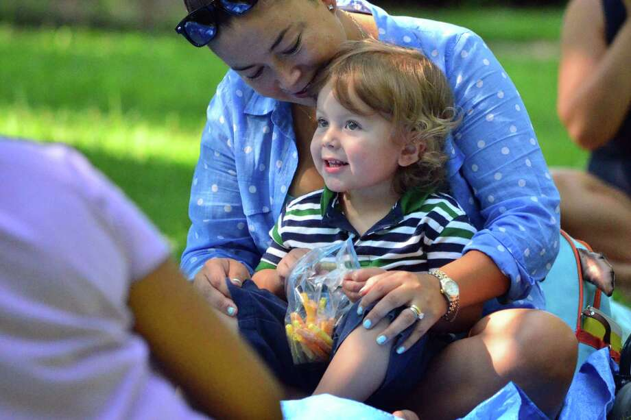 Ethan Sette, 21 months, listens to childrens librarians from the Darien Library during Stories by the Pond on August 5. The library teamed up with the Park and Recreation Department for the 30-minute story telling event at Tilley Pond Park. The three librarians sang songs with the children and told three stories. Photo: Megan Spicer / Darien News