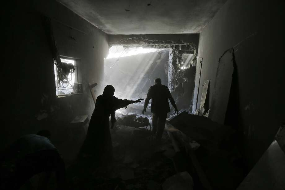 A Palestinian family searches for their belongings amid the rubble of their home, destroyed by air strikes. Photo: Lefteris Pitarakis, Associated Press