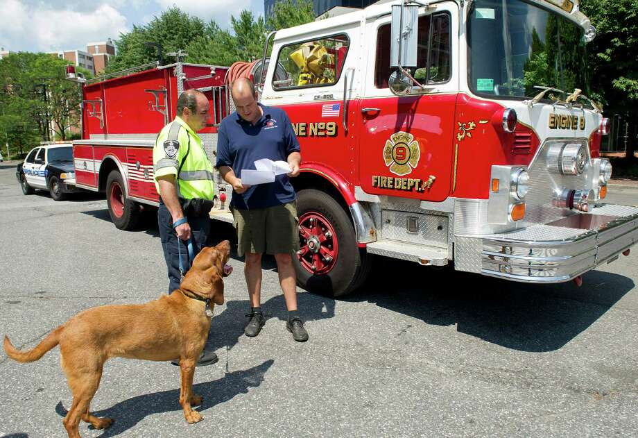 Stamford police officer Don Holden, right, reviews the route to Yocum County, Kentucky, with officer Mark Vitti and his police dog, Cleo, in Stamford, Conn., on Tuesday, August 5, 2014. Holden and Vitti are driving the fire truck from Cromwell, Conn., to the small Kentucky town for donation. Photo: Lindsay Perry / Stamford Advocate