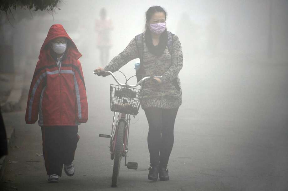 A woman walks with her child on a street as schools were closed due to the heavy smog in Jilin, northeast China's Jilin province on October 22, 2013. Thick smog enveloped China's northeast area for a third day on October 22.   CHINA OUT     AFP PHOTOSTR/AFP/Getty Images Photo: Str, AFP/Getty Images