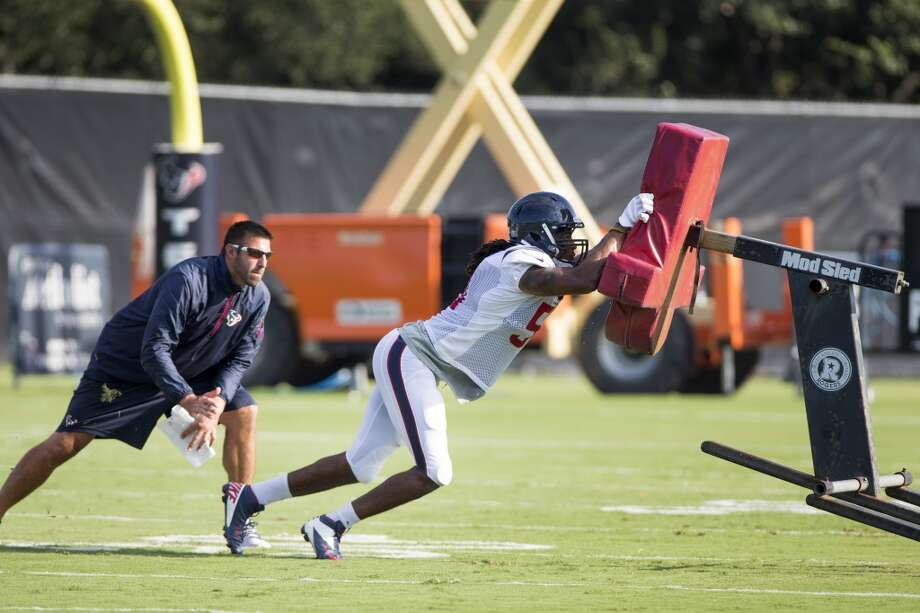 Texans linebacker Paul Hazel (51) hits a blocking sled as linebackers coach Mike Vrabel looks on. Photo: Brett Coomer, Houston Chronicle