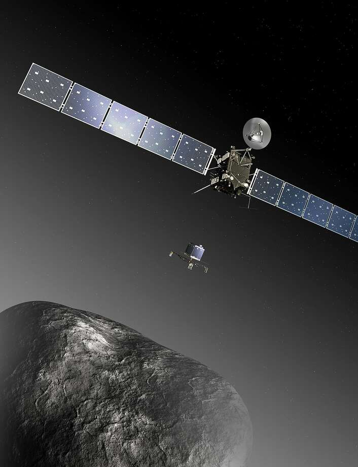 This image provided by the European Space Agency ESA shows an artist's impression of the Rosetta orbiter deploying the Philae lander to comet 67P/Churyumov–Gerasimenko. The image is not to scale; the Rosetta spacecraft measures 32 m across including the solar arrays, while the comet nucleus is thought to be about 4 km wide. Scientists at the European Space Agency are expecting their comet-chasing probe Rosetta to wake from almost three years of hibernation at 11 a.m. Monday Jan. 20, 2014 (1000 GMT; 5 a.m. EST) and phone home to say all is well. (AP Photo/ESA, C.Carreau, File) Photo: Uncredited, Associated Press