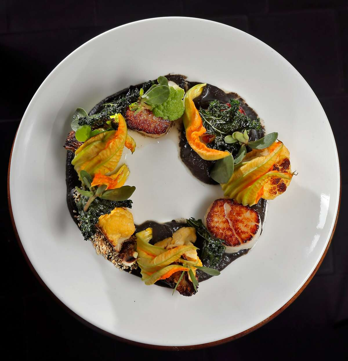 La Urbana in San Francisco features an entree, Cast Iron Scallop with cauliflower, sesame seeds, squash blossoms and kale, which features a Mexican delicacy, huitlacoche. Huitlacoche is