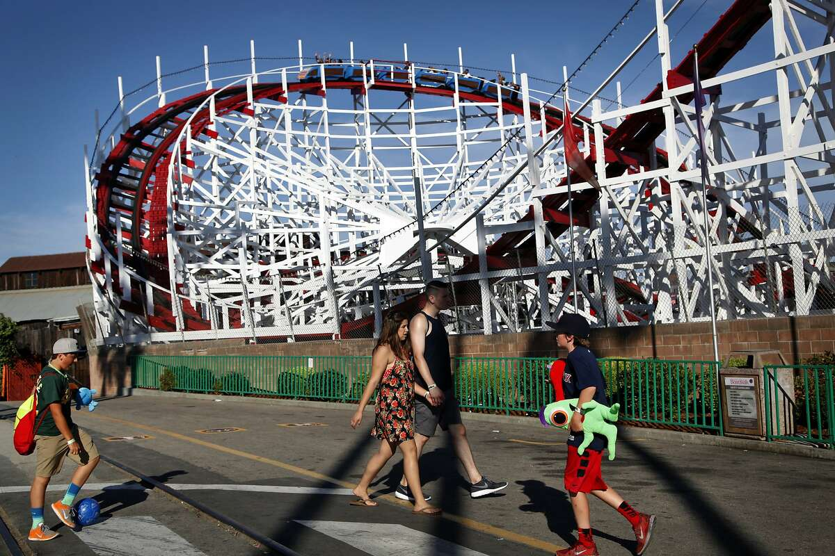 People head to the Santa Cruz Beach Boardwalk as the Giant Dipper wooden roller coaster looms above.