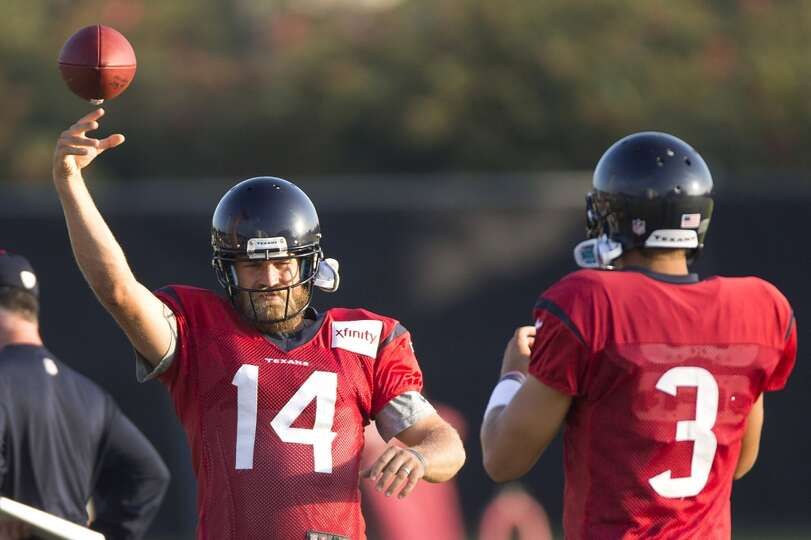 Quarterbacks Ryan Fitzpatrick (14) and Tom Savage (3) play catch before practice.