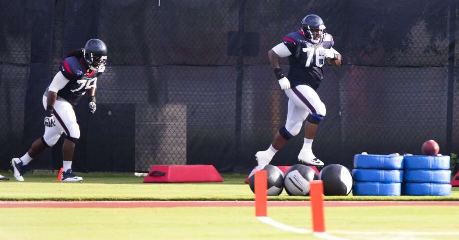 Tackles Derek Newton (75) and Duane Brown (76) run through a drill. Photo: Brett Coomer, Houston Chronicle