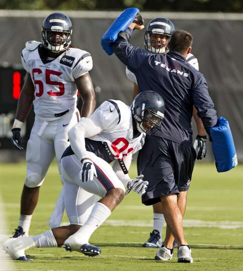 Texans linebacker Lawrence Sidbury (91) runs around linebackers coach Mike Vrabel during a drill.