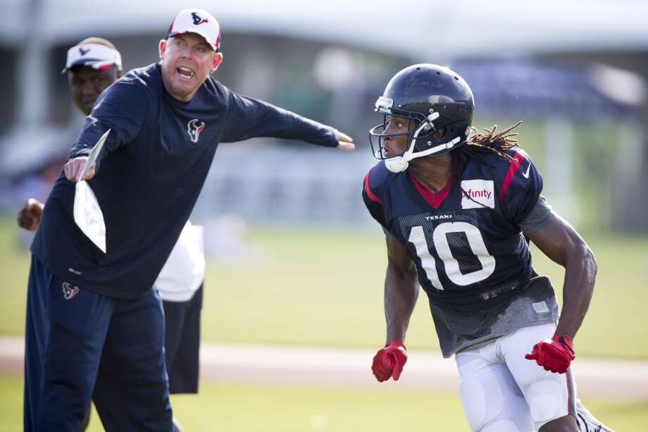 Quarterbacks coach George Godsey, left, runs a drill with wide receiver DeAndre Hopkins (10). Photo: Brett Coomer, Houston Chronicle