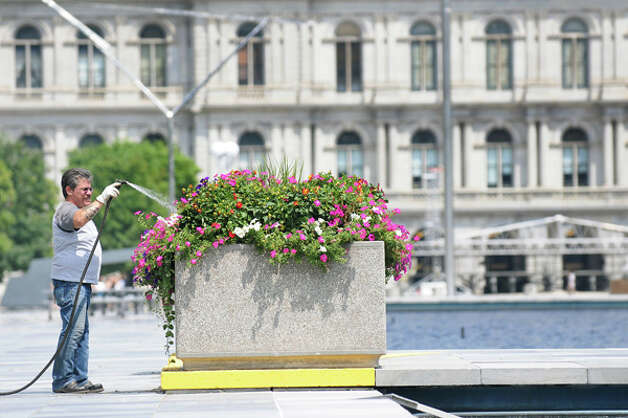 A grounds worker with the Office of General Services waters the flowers on Tuesday, Aug. 5, 2014, on the Empire State Plaza in Albany, N.Y. (Cindy Schultz / Times Union) Photo: Cindy Schultz, Albany Times Union / 00028056A