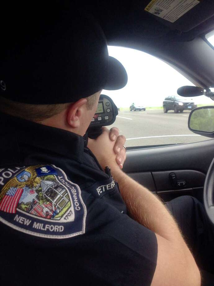 Officer David Petersen points a laser device for speed detection of coming vehicles while on enhanced speed enforcement patrol on Danbury Road. Photo: Susan Tuz / The News-Times