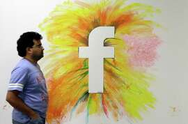 In this June 11, 2014 photo, a man walks past a Facebook logo in an office on the Facebook campus in Menlo Park, Calif. Facebook reports quarterly financial results on Wednesday, July 23, 2014.(AP Photo/Jeff Chiu)