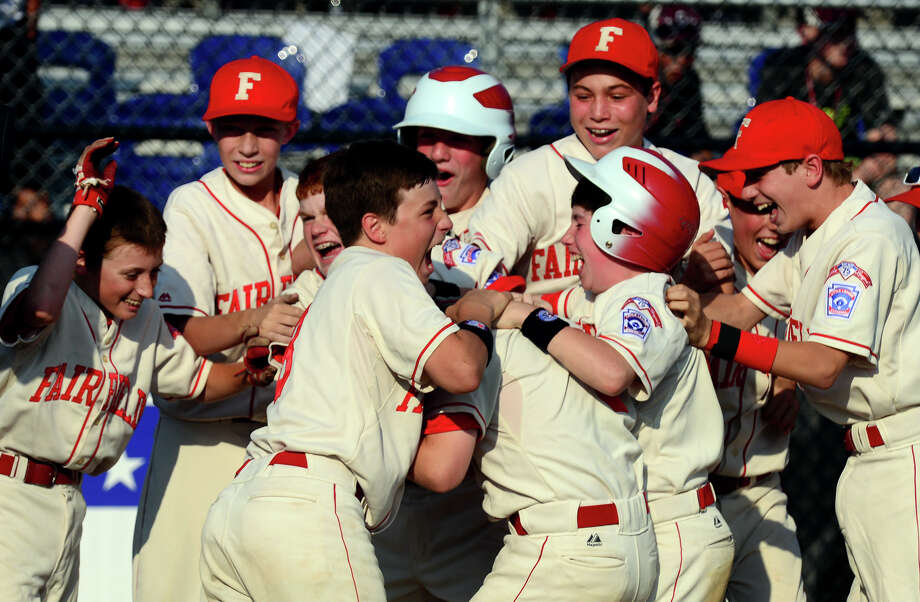 Fairfield American team members surround Jamie Flink as they celebrate it's win over Rhode Island, during New England little league tournament action in Bristol, Conn. on Saturday August 2, 2014. Flink hit a 2 run home run to beat Rhode Island 5-3. Photo: Christian Abraham / Connecticut Post