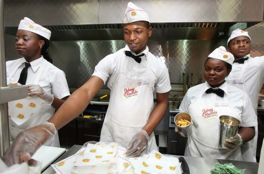 FILE - In this Wednesday, Jan. 23, 2013, file photo, workers prepare to serve hamburgers and fries at Johnny Rockets restaurant in Lagos, Nigeria. Years of solid economic growth, gradual economic reforms and energy discoveries have transformed Africa from a basket case into one of the world's hottest markets. (AP Photo/Sunday Alamba, File) ORG XMIT: NYBZ199 Photo: Sunday Alamba / AP