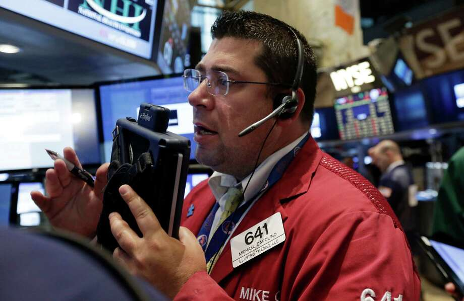 Trader Michael Capolino works on the floor of the New York Stock Exchange, Tuesday, Aug. 5, 2014. U.S. stock prices are opening lower as traders digest some mixed corporate earnings and a weak indicator on the Chinese economy. (AP Photo/Richard Drew) ORG XMIT: NYRD111 Photo: Richard Drew / AP