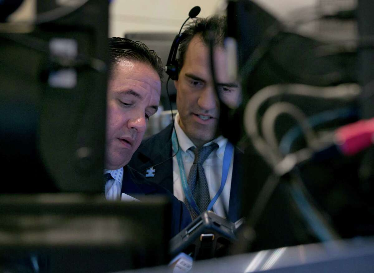 Traders Tommy Kalikas, left, and Gregory Rowe consult their handheld devices on the floor of the New York Stock Exchange. (AP Photo/Richard Drew)