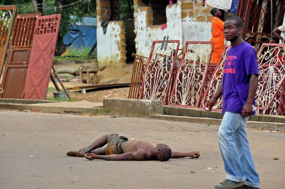 The lifeless body of a man lays unattended in the street as locals suspect him of dying from the deadly Ebola virus, as government warns the public not to leave Ebola victims in the streets in the city of Monrovia, Liberia, Tuesday,  Aug. 5, 2014.  A second American aid worker infected with Ebola arrived Tuesday in Atlanta, where doctors will closely monitor the effect of an experimental drug she agreed to take even though its safety was never tested on humans. Nancy Writebol arrived from Monrovia, Liberia, in a chartered plane at Dobbins Air Reserve Base and will join Dr. Kent Brantly in the isolation unit at Emory University Hospital, just downhill from the U.S. Centers for Disease Control and Prevention. (AP Photo/Abbas Dulleh) Photo: Abbas Dulleh, STR / AP