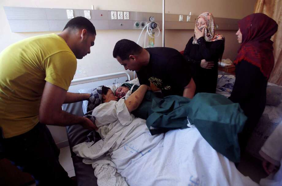 Mohammed al-Bakri brings the body of his 3-year-old son Kamal  on Tuesday to the boy's wounded mother, Dua, at the Shifa hospital in Gaza City. Photo: Hatem Moussa, STF / AP