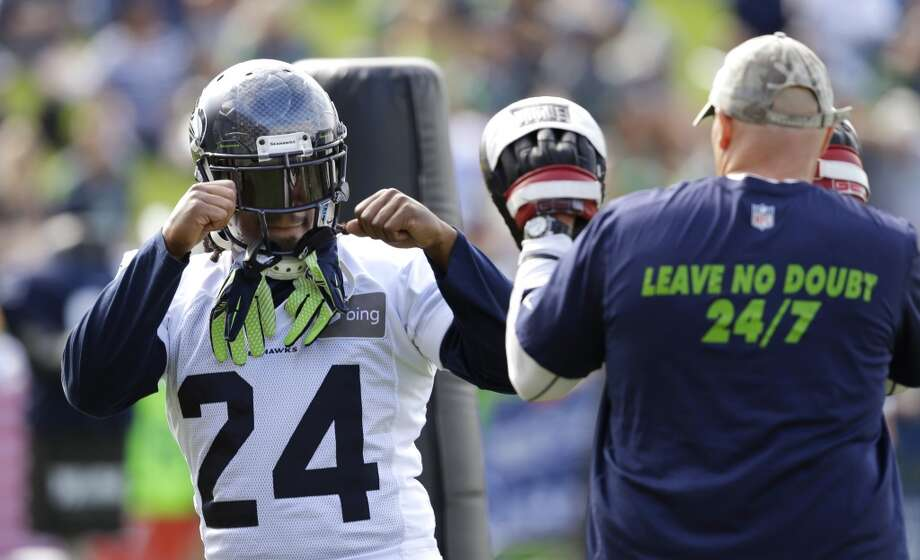 Seahawks running back Marshawn Lynch, left, squares off in a joking manner with defensive coordinator Dan Quinn during practice Tuesday, Aug. 5, in Renton. Photo: Ted S. Warren, Associated Press
