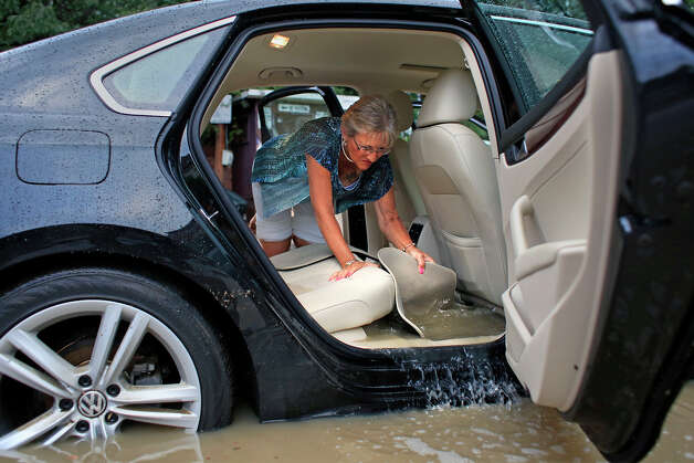 Anna May Quirk pushes floodwater out of the interior of her car with a floor mat after a storm hit the area, on Tuesday, August 5, 2014 in Albany, N.Y.  (Tom Brenner/ Special to the Times Union) Photo: Tom Brenner, Albany Times Union / ©Tom Brenner/ Albany Times Union