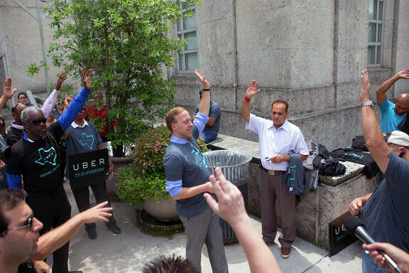 Uber executive Chris Nakutis, center, leads a rally for drivers and riders Tuesday outside City Hall. The City Council will vote Wednesday on whether to allow the new ride-share services on Houston's streets.