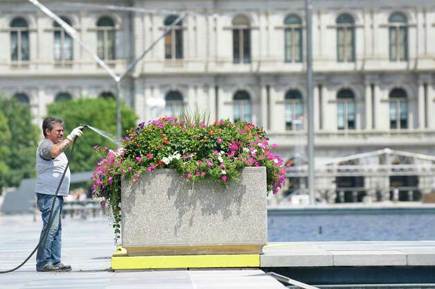 A grounds worker with the Office of General Services waters the flowers on Tuesday, Aug. 5, 2014, on the Empire State Plaza in Albany, N.Y. (Cindy Schultz / Times Union) Photo: Cindy Schultz / 00028056A