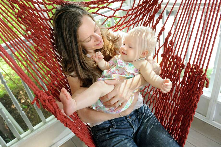 Allison Tallman, left, and her daughter, Claire Tallman, 10 months, swing on the porch on Tuesday, Aug. 5, 2014, at their home in Watervliet, N.Y. Claire was born in a birthing tub. (Cindy Schultz / Times Union) Photo: Cindy Schultz / 00028016A