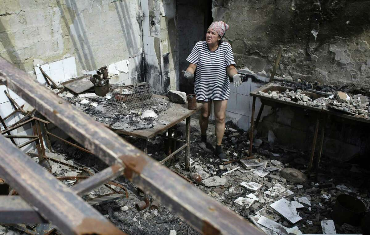 A woman gestures as she removes debris from a cafe, which was destroyed during fighting between Ukrainian forces and pro-Russian militants, in the eastern Ukrainian city of Slavyansk.