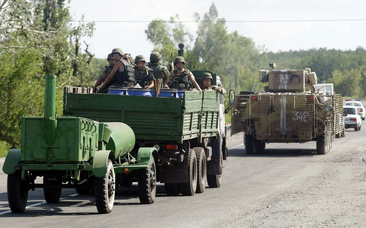 Ukrainian servicemen sit in an armored personnel carrier near Slavyansk in eastern Ukraine. Miles to the south, terrified residents fled the besieged rebel bastion of Donetsk.