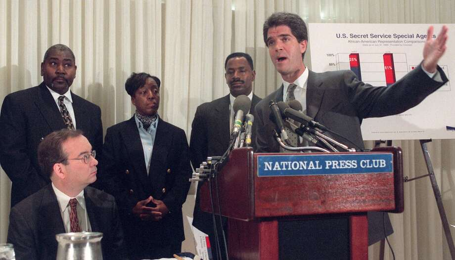 Attorney John Reiman, right, announces the filing of a class action racial discrimination suit with the Equal Employment Opportunity Commission against the United States Secret Service on behalf of African-American Secret Service Agents at the National Press Club in Washington Thursday Feb. 24, 2000. From left, attorney David Shaffer, seated, Secret Service agents John Turner, Yvette Summerour and Ray Moore. (AP Photo/Leslie Kossoff)   HOUCHRON CAPTION (02/25/2000):  The three agents who are suing the Secret Service stand behind attorney John Reiman as he announces the filing of the lawsuit Thursday. Photo: LESLIE E. KOSSOFF, STR / AP