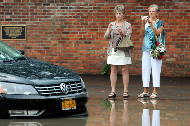 Sue Michalski, left, and Anna May Quirk, right, take pictures of Anna's submerged car, on Sheridan Avenue, on Tuesday, August 5, 2014 in Albany, N.Y.  Heavy flooding hit the area after a storm on Tuesday evening.  (Tom Brenner/ Special to the Times Union) Photo: Tom Brenner / ©Tom Brenner/ Albany Times Union