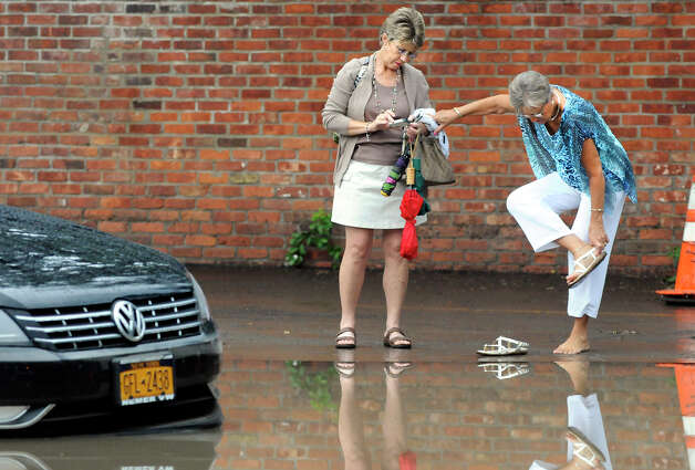 Sue Michalski, left, holds Anna May Quirk's belongings as she attempts to walk into floodwaters to get inside of her submerged car, in a parking lot on Sheridan Avenue, on Tuesday, August 5, 2014 in Albany, N.Y.  Heavy flooding hit the area after a storm on Tuesday evening.  (Tom Brenner/ Special to the Times Union) Photo: Tom Brenner / ©Tom Brenner/ Albany Times Union