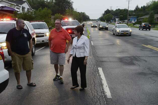 Colonie Town Supervisor Paul Mahan, right, inspects flood damage at the intersection of Troy Schenectady Rd. (Route 2) and Monroe Ave. Tuesday afternoon, Aug. 5, 2014, in Colonie, N.Y. A fast moving storm caused flooding and damage throughout the Capital Region. (Will Waldron/Times Union) (Will Waldron/Times Union) Photo: WW