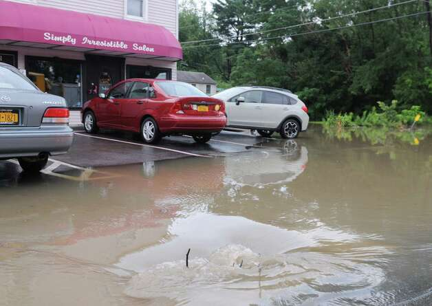 Storm water syphons into a drain at the intersection of Troy Schenectady Rd. (Route 2) and Monroe Ave. Tuesday afternoon, Aug. 5, 2014, in Colonie, N.Y. A fast moving storm caused flooding and damage throughout the Capital Region. (Will Waldron/Times Union) Photo: WW