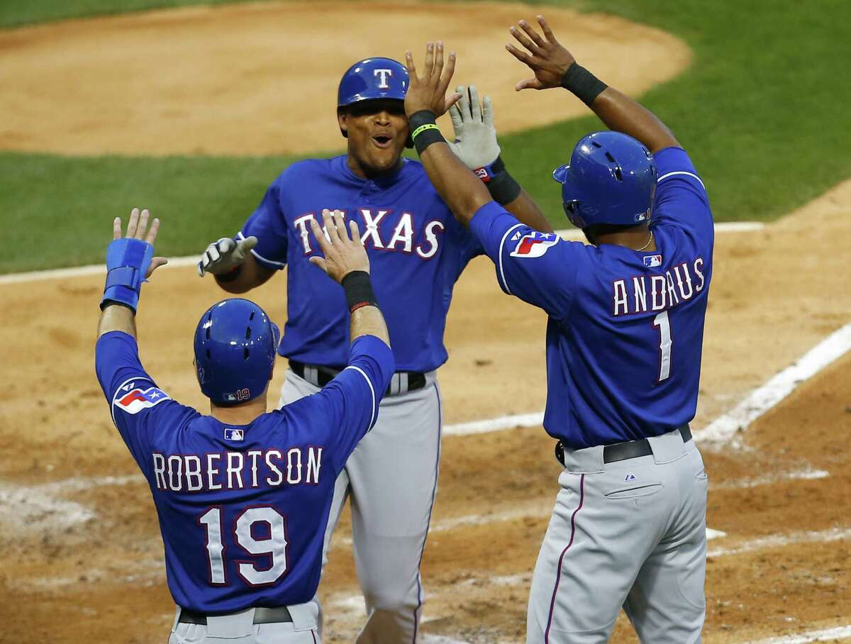 Rangers left fielder Daniel Robertson and shortstop Elvis Andrus congratulate third baseman Adrian Beltre after they all scored in Tuesday's 16-0 rout of the White Sox in Chicago.