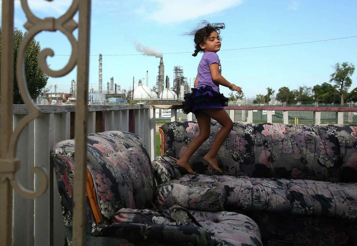 Candela Vega, 6, jumps on the outdoor couches in their home across the street from Valero Refinery on Tuesday, Aug. 5, 2014, in Houston. The EPA is holding public hearings at the Galena Park Community Center.