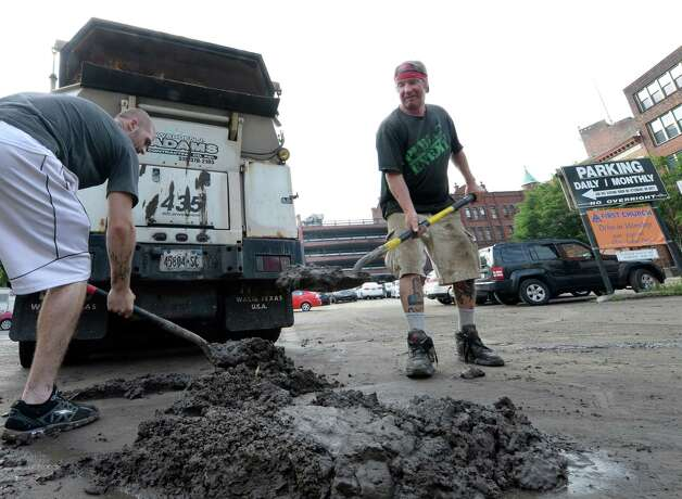 Bryan Wilson, left, and Roberts Alberts of Adam's Contracting remove some of the approximately 2 inches of mud that accumulated from Tuesday's flooding at the Maiden Lane Parking Lot Wednesday morning, Aug. 6, 2014, in Albany, N.Y.   (Skip Dickstein/Times Union) Photo: SKIP DICKSTEIN