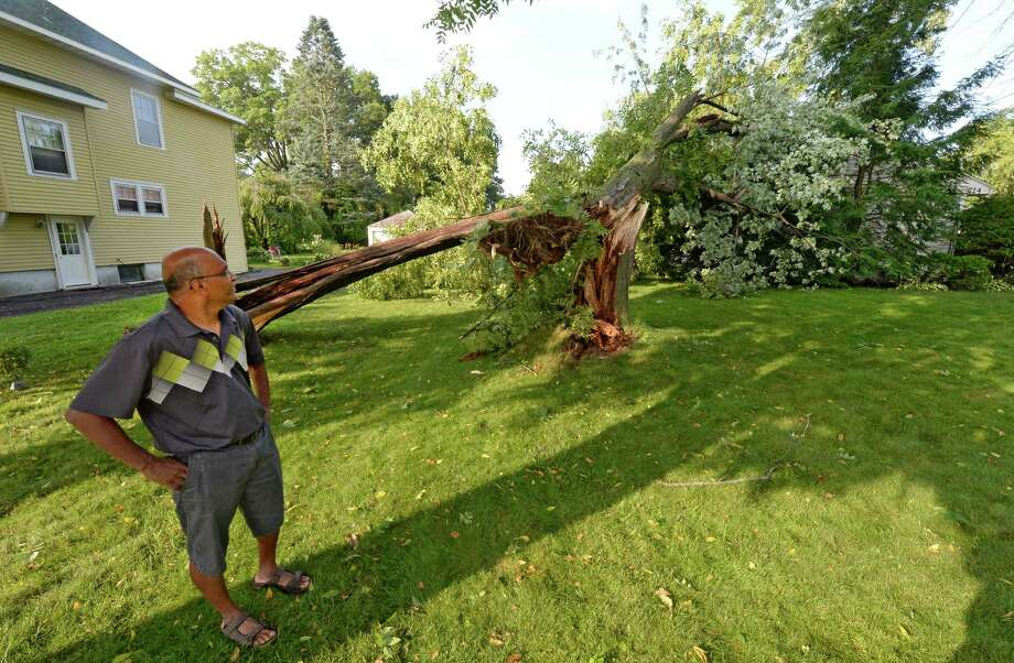 Homeowner Kris Rao surveys the storm damage Wednesday morning, Aug. 6, 2014, after two trees fell on his home Tuesday at 724 Western Avenue in Albany, N.Y.   (Skip Dickstein/Times Union) Photo: SKIP DICKSTEIN
