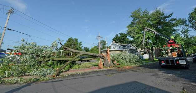 A DGS tree removal worker takes the remains of two trees that toppled at the intersection of Whitehall Road and Ten Eyck Wednesday morning, Aug. 6, 2014, as a result of a Tuesday afternoon storm in Albany, N.Y.   (Skip Dickstein/Times Union) Photo: SKIP DICKSTEIN