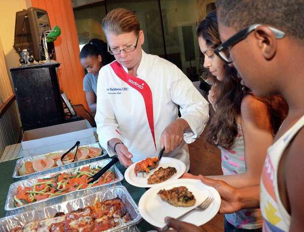 RPI's executive chef, Jackie Baldwin, center, serves up a healthy lunch to north Troy teens at the Sanctuary for Independent Media's Uptown Summer program Wednesday July 30, 2014, in Troy, NY.  (John Carl D'Annibale / Times Union) Photo: John Carl D'Annibale / 00027986A