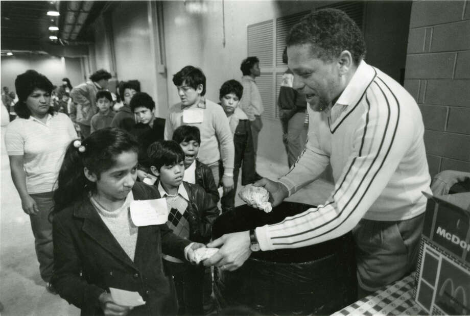 Rep. Mickey Leland hands out burgers to children at a Houston-area Christmas party on Dec. 22, 1986. Mickey Leland, a Democratic congressman from Texas 18th District, died Aug. 7, 1989 at age 44 when a plane he was on crashed during a mission trip in Fugnido, Ethiopia. Photo: Houston Chronicle File Photo