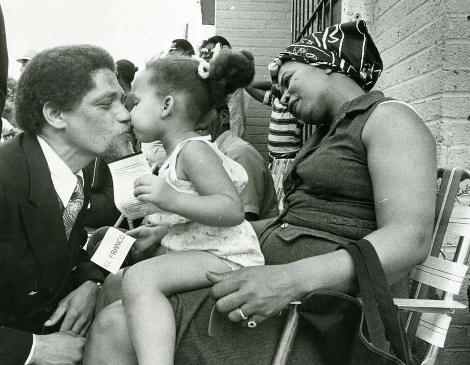 Rep. Mickey Leland gives a kiss to Annie Neal, 2, whos is seated on the lap of her mother Fay, during an 18th Congressional District race campaign visit in May 1978. Mickey Leland, a Democratic congressman from Texas 18th District, died Aug. 7, 1989 at age 44 when a plane he was on crashed during a mission trip in Fugnido, Ethiopia. Photo: Houston Chronicle File Photo