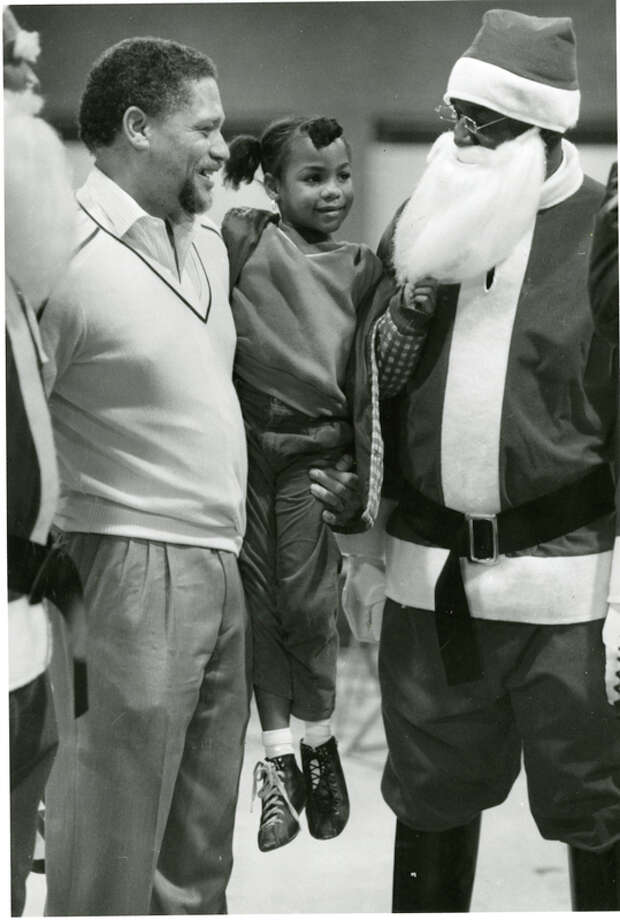 Rep. Mickey Leland holds up Rona Bush, 6, so she can tug on Santa's beard Dec. 22, 1986. Mickey Leland, a Democratic congressman from Texas 18th District, died Aug. 7, 1989 at age 44 when a plane he was on crashed during a mission trip in Fugnido, Ethiopia. Photo: Houston Chronicle File Photo
