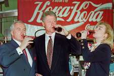 US President Bill Clinton (C), First Lady Hillary Rodham Clinton (R) and Michael O'Neill, Coca-Cola Deputy Region Manager in Russia, drink a Coca-Cola May 11, 1995, in Moscow, during their visit to the Coca-Cola factory in the Russian capital. AFP PHOTO YURI KADOBNOV