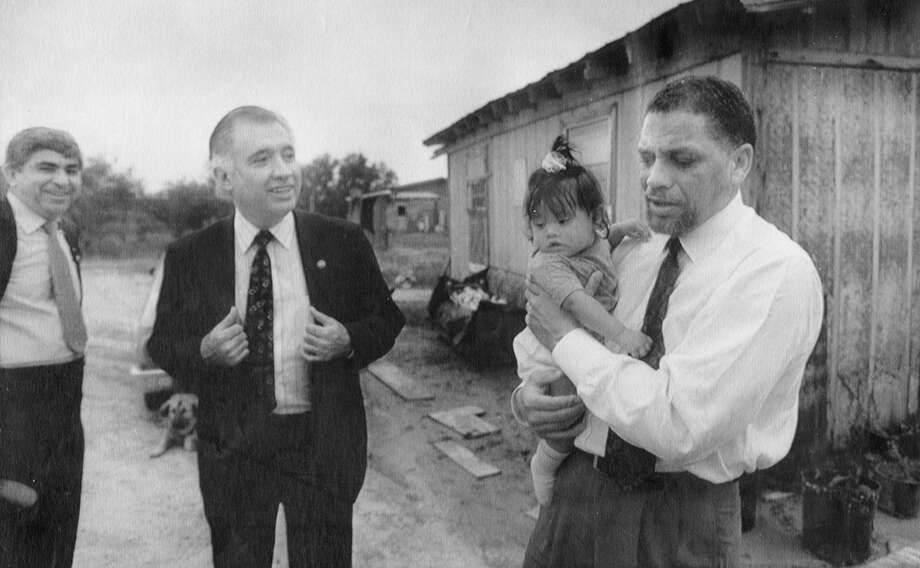 U.S. Rep. Mickey Leland, right, holds a little girl  during a May 1989 tour of a colonia in Eagle Pass, Texas. U.S. Reps. Albert Bustamante, D-San Antonio, far left, and Solomon Ortiz, D-Corpus Christi, were part of a congressional panel with Leland looking into colonia residents' problems. Leland, a Democratic congressman from Texas 18th District, died Aug. 7, 1989 at age 44 when a plane he was on crashed during a mission trip in Fugnido, Ethiopia. (AP / Dennis Dunleavy) Photo: AP, UPI Photos