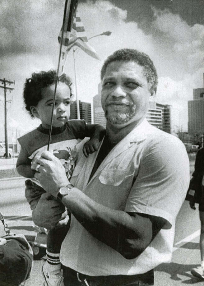 U.S. Rep. Mickey Leland, carrying his 3-year-old son, Jarrett, during a parade in Houston. Leland, a Democratic congressman from Texas 18th District, died Aug. 7, 1989 at age 44 when a plane he was on crashed during a mission trip in Fugnido, Ethiopia. (UPI / Marc Morrison) Photo: AP, UPI Photos