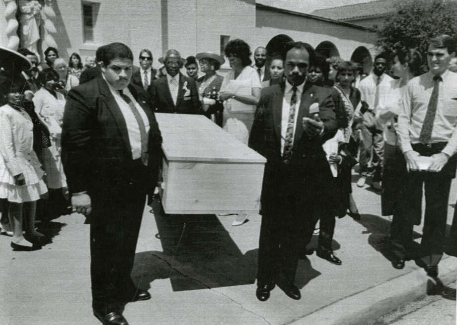 A symbolic wooden coffin for Congressman Mickey Leland is carried from St. Anne's Catholic Church after a funeral Mass in Houston while Leland's body was still in Africa. Leland, a Democratic congressman from Texas 18th District, died Aug. 7, 1989 at age 44 when a plane he was on crashed during a mission trip in Fugnido, Ethiopia. (UPI / Marc Morrison) Photo: AP, UPI Photos