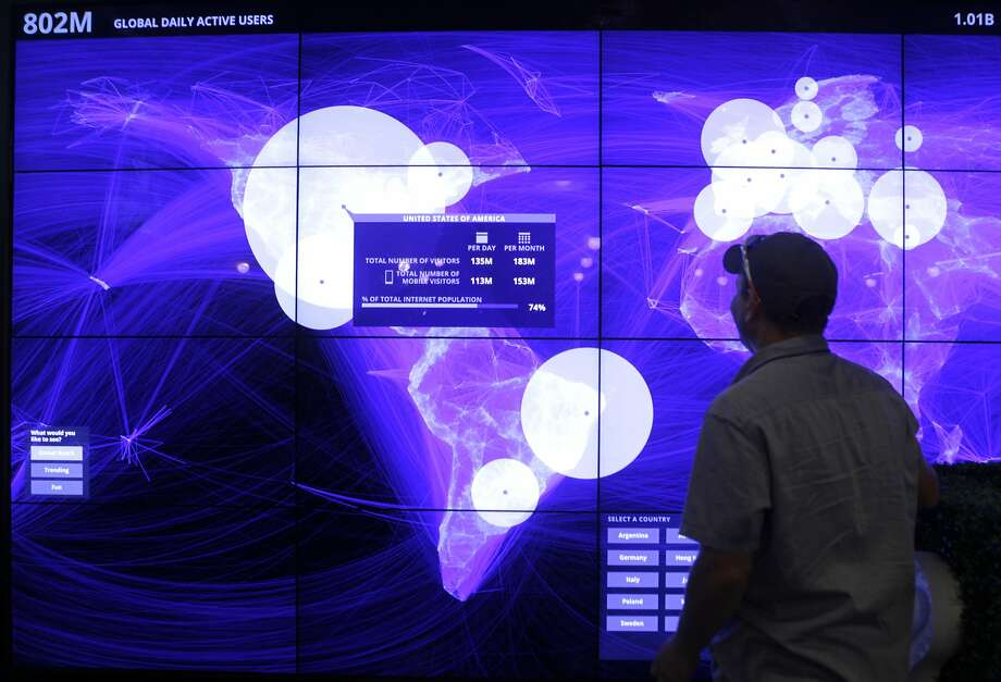 Eric Vaughn checks out a monitor that displays activity by Facebook users worldwide during a small-business conference. Photo: Paul Chinn, The Chronicle