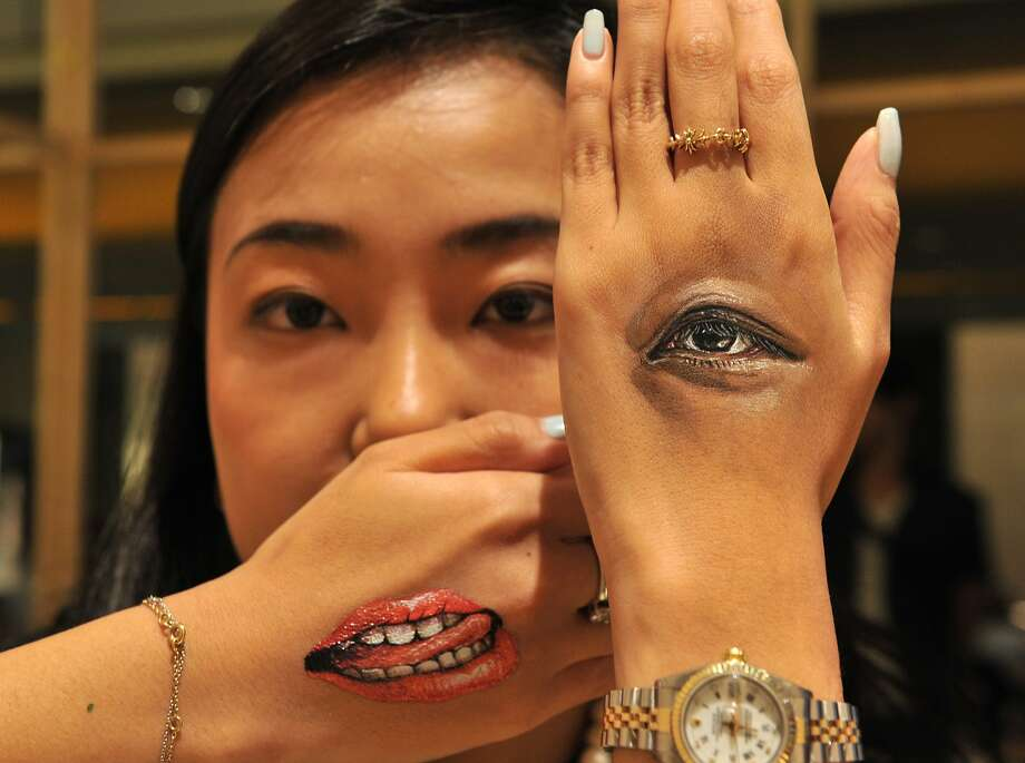 "Is she winking at me or just making a fist?A woman shows paintings of her eye and mouth done by Japanese body-painting artist Hikaru Cho at the ""Future en-nichi"" art event in Tokyo. Photo: Yoshikazu Tsuno, AFP/Getty Images"